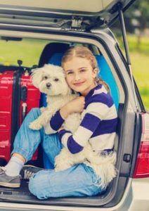 Una chica que viaja en un coche con un perro